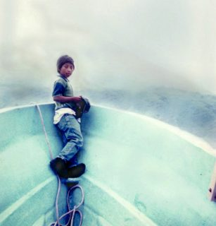 A boy leans into the inside bow of a boat, looking back