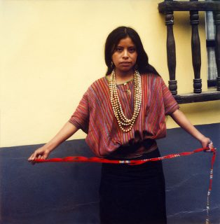 A girl in beautiful Mayan garments and beads holds a bright red woven sash, Antigua, Guatemala