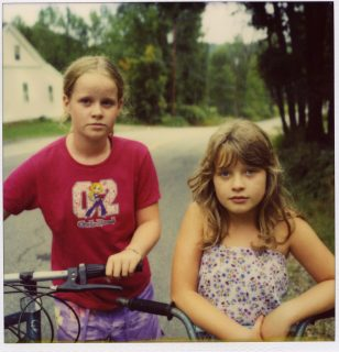 Two young girls stand expressionless, leaning on the handlbars of bicycles