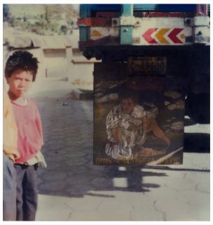 A boy stands next to a square, printed sign leaning on a truck