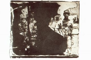 An artistically developed photo depicts soldiers through bleeding patches of exposure