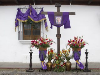 A religious vigil of a cross and purple saches lines the edge of the street