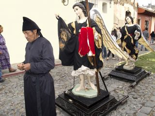 A man in black robes stands in front of two statues in a line