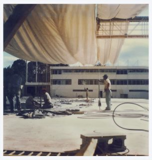 Canvases drape over men working at an outside construction site, color Polaroid photo