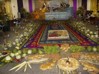 Offerings line the outside edge of a rug with a cake in the center frosted with a picture of Jesus