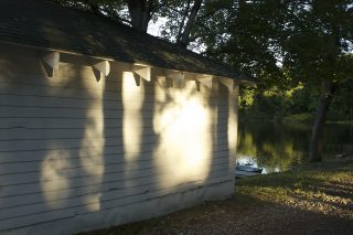 Trees cast shadows on a boathouse in Maine