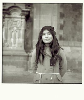 Black and white photo of a Mexican girl in front of a church