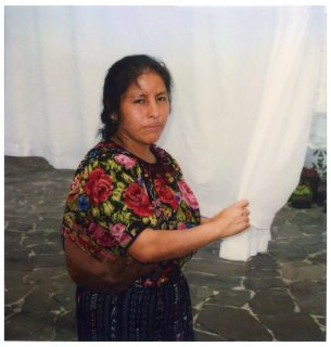 A woman, dressed in Mayan clothing, holds a clean linen on a drying line