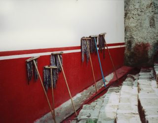 Wet mops lean against a white and red wall