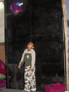 A boy looks up a balloon he is holding