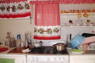 old-fashioned kitchen with red checkered and flowered curtain, pots on small stove, drying rack, kitchen utensils, tea service on shelf, Aruba